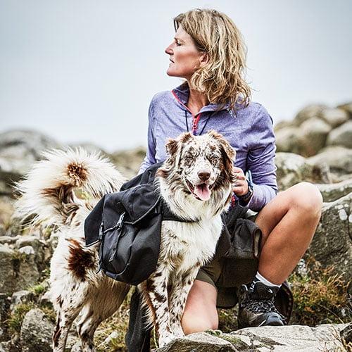 Miljøfoto av hund med kløv og dame ute i naturen